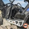 A utv with door open is parked on the side of a dirt field