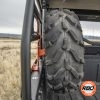 A closeup of a spare tire mounted to a bobcat spare tire mount in bed of utv