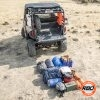 A pile of luggage sitting on top of a dirt field outside UTV