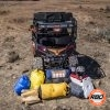 A pile of luggage sitting outside of a UTV